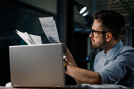 Working man with papers and laptop Stock Photo