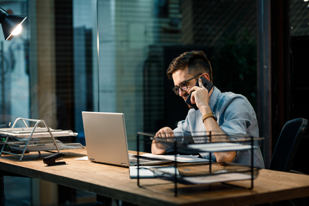 Casual man having call in office