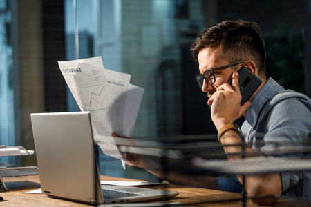 Confident man with papers speaking on phone Stock Photo