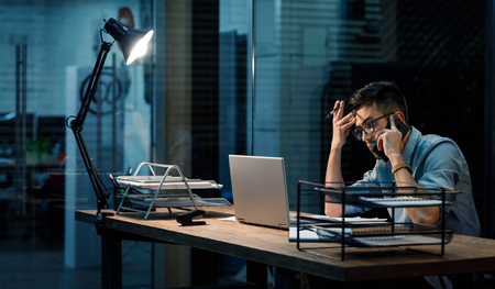 Busy man in office speaking on phone
