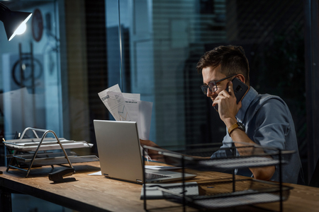 Employee with phone using laptop