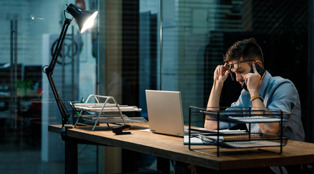Tired man in office with laptop