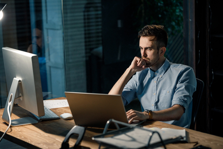 Thoughtful employee leaning on hand at laptop Stock Photo