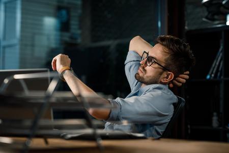 Hombre trabajando hasta tarde en la oficina comprobando el tiempo