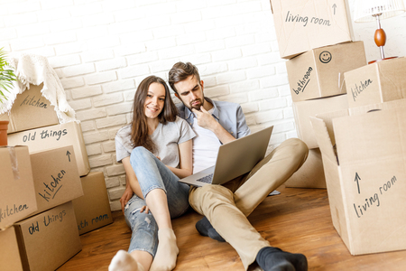 Charming couple with laptop relocating