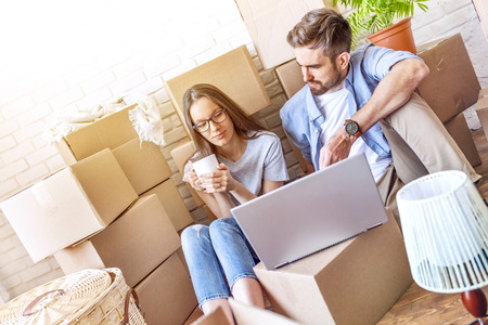 Chilling couple with coffee and packed boxes