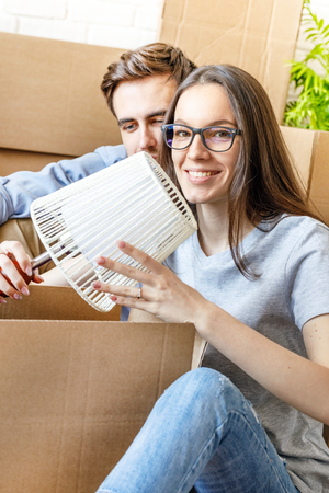 Content woman packing lamp for moving