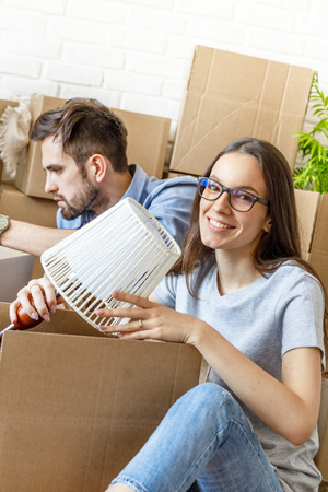 Content girl packing stuff with man
