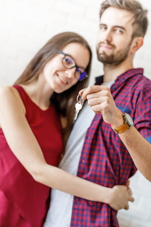 Excited couple holding key from new apartment