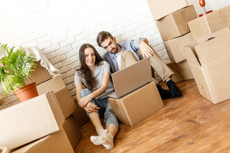 Young couple with laptop and moving boxes Stock Photo