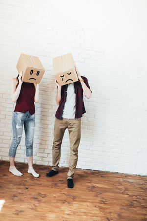 Happy couple covering head with boxes