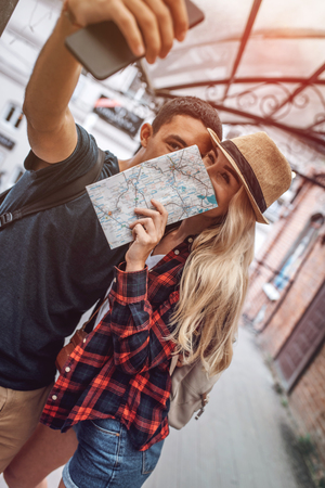 Amorous couple with map taking selfie outdoors