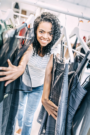 Playful black woman behind hangers with clothes 版權商用圖片