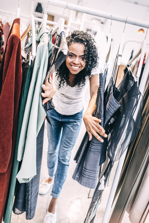 Happy black woman between hangers with clothes