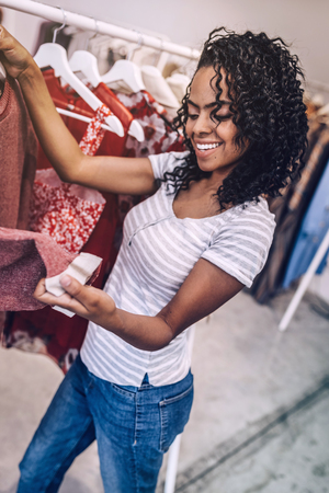 Smiling woman checking quality of clothes