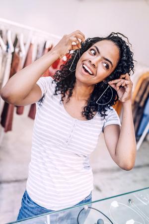Playful woman trying earrings in shop