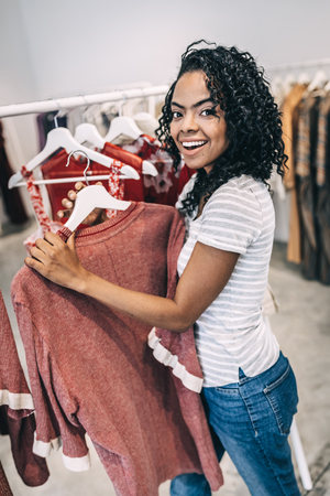 Smiling woman standing with hanger in shop