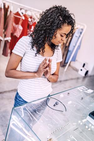 Pensive woman choosing modern jewelry