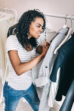 Black woman checking trendy shirt in shop