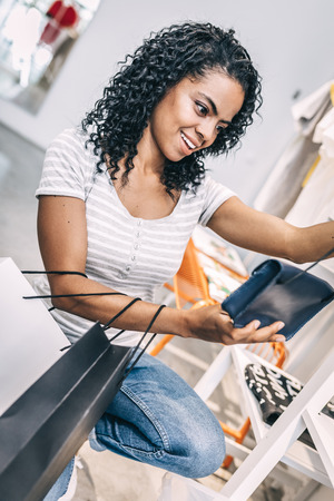 Excited woman holding trendy clutch in shop