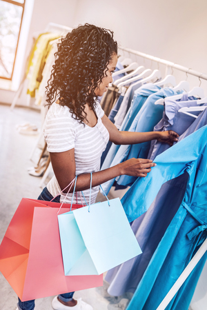 Casual woman with shopping bags exploring clothes