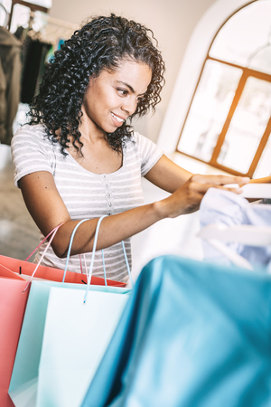 Smiling woman choosing clothes in shop