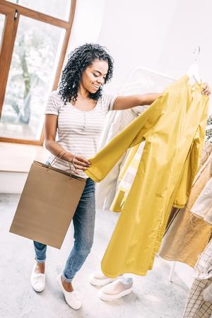 Woman exploring trendy dress in shop Stock Photo