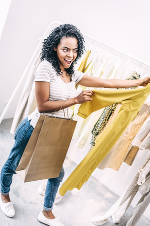 Content woman with bright dress in shop