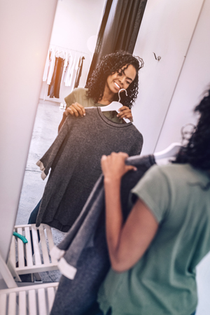 Content woman with clothes in front of mirror