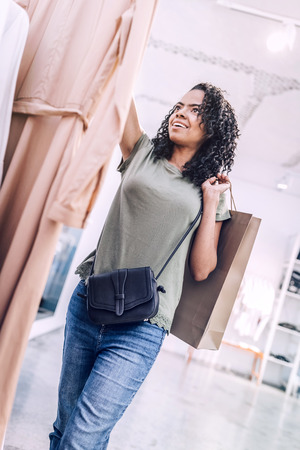 Excited woman holding hanger with dress in shop Stock Photo