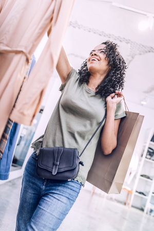Cheerful woman holding stylish dress in boutique