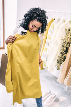 Woman trying modern bright dress in shop