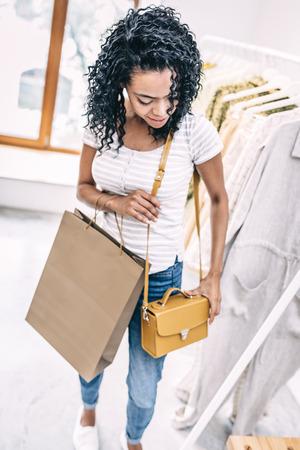 Smiling woman trying trendy handbag in shop