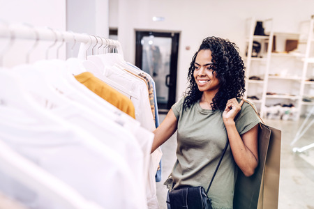 Smiling woman looking at clothes on hangers Stock Photo