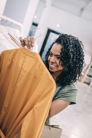 Happy woman reading label on trendy dress
