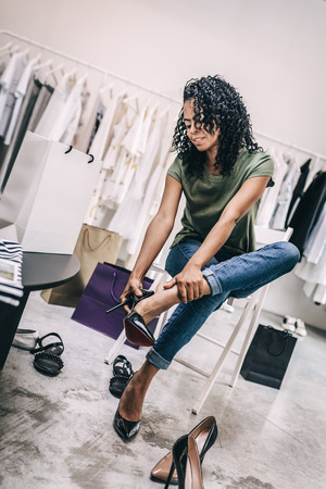 Modern woman shopping in shoes store