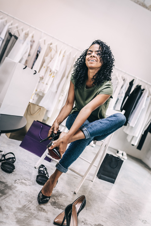 Casual happy woman trying on shoes