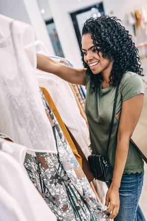 Smiling woman excited with dress in shop