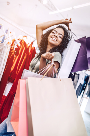 Laughing woman with bags in store
