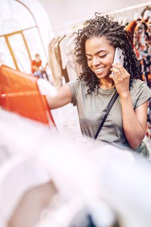 Black woman speaking on phone in shop