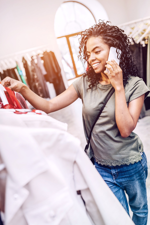 Woman talking on phone while choosing clothes