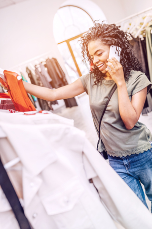 Smiling woman shopping in boutique and chatting on phone Stock Photo