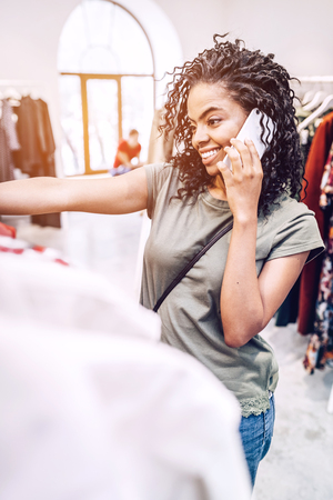 Smiling woman in shop speaking on phone Stock Photo