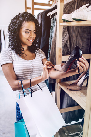 Smiling woman checking stylish heels in store