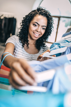 Smiling woman choosing new clothes