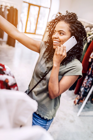Smiling woman speaking on phone in shop