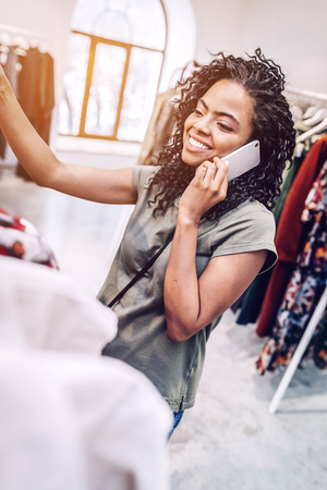 Ethnic woman speaking on phone in boutique