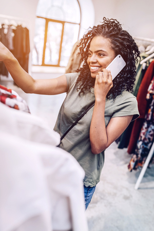 Casual woman speaking on phone in store
