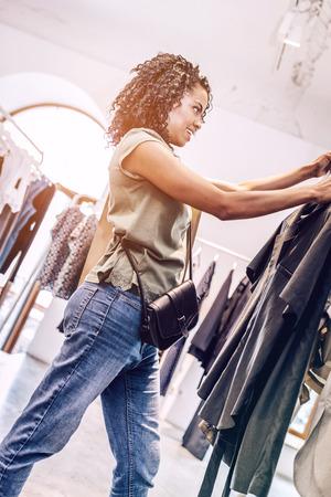 Black woman choosing clothes in shop