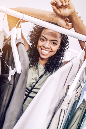 Smiling black woman near hangers in shop Stock Photo
